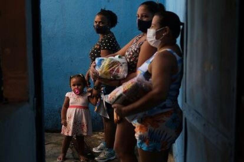 Vecinas de una favela de Río de Janeiro, tras recibir donaciones en una escuela, el pasado abril.