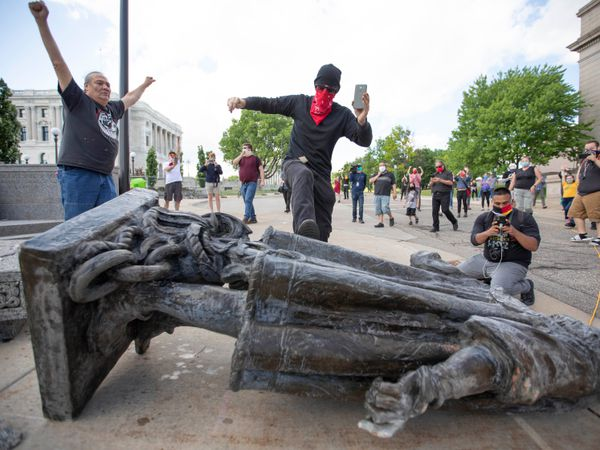 FILED - 10 June 2020, US, Saint Paul: A man kicks the statue of Christopher Columbus as it lays down on the ground after being pulled down by Native American activists at the Minnesota State Capitol. Photo: Chris Juhn/ZUMA Wire/dpa  10/06/2020 ONLY FOR USE IN SPAIN