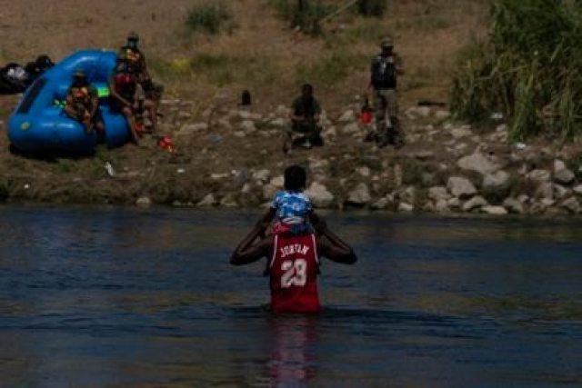 Un hombre haitiano y su hijo cruzan el Río Bravo hacia Del Río (Texas), este jueves.