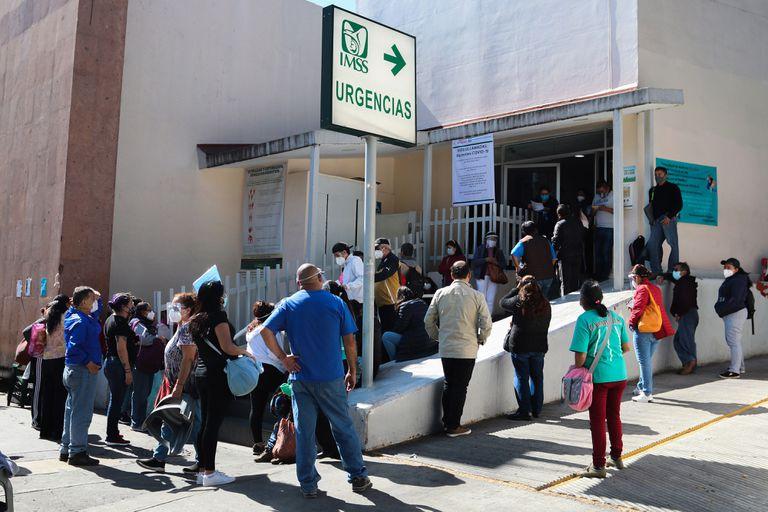 Familiares esperan informes de pacientes diagnosticados con covid-19 afuera de un hospital, en la Ciudad de México.