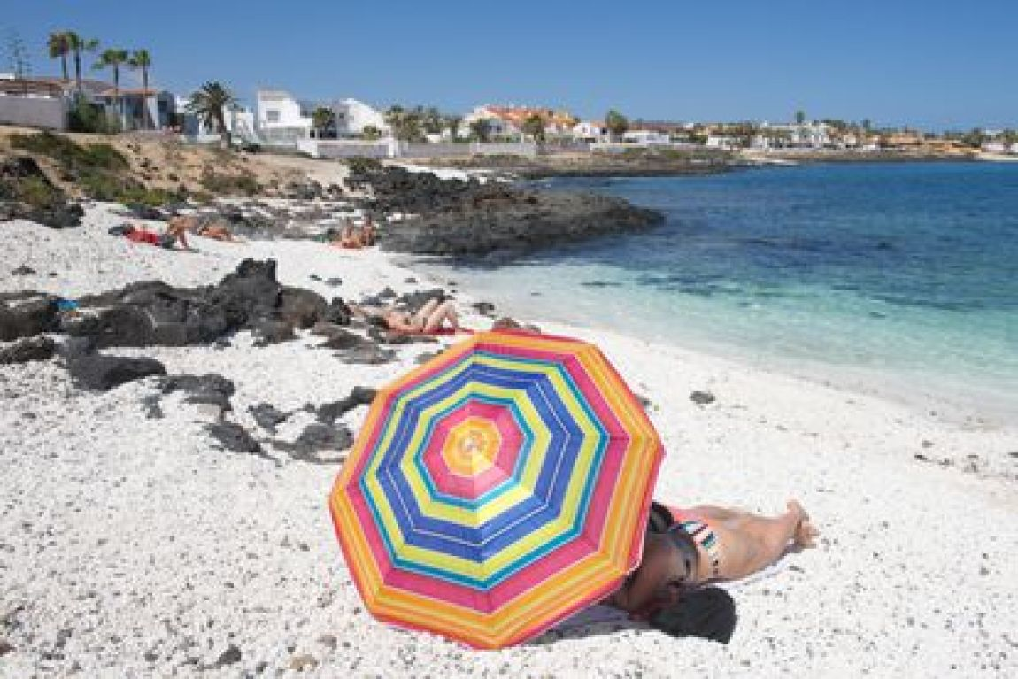 Tourists enjoying a day at the beach in the town of Corralejo, in the north of Fuerteventura.