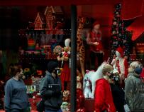 A group of tourists walk past the Macy's Christmas window in an unusually empty city.