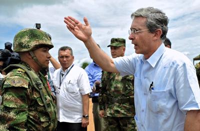 Álvaro Uribe gesticula ante un soldado durante una visita a una  base militar en el departamento de Meta en 2009. - AP