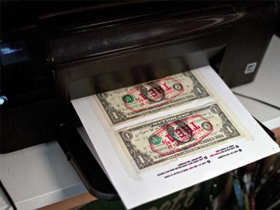 Con una impresora y una plantilla, un grupo de indignados anima a imprimir sus mensajes de un dólar.