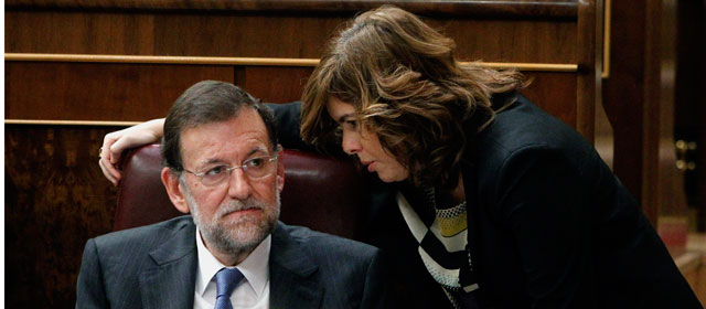 Rajoy escucha a Soraya Sáenz de Santamaría durante la segunda jornada del debate de investidura.