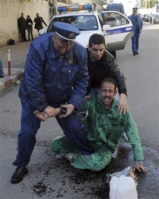Un policía y un viandante impiden que un parado se prenda fuego durante una protesta el 6 de febrero. EFE