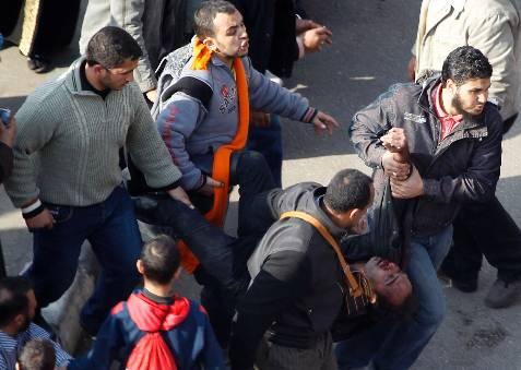 Manifestantes contra Mubarak llevan a un herido en los choques. REUTERS / Amr Abdallah Dalsh