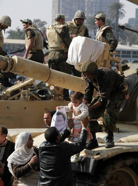 Un soldado egipcio devuelve a unos padres a su niña, con un retrato del presidente egipcio en la mano, tras hacerse una foto junto a ella en el vehículo blindado. EFE/Jim Hollander
