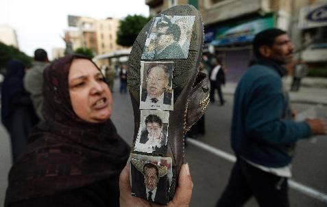 Un detractor de Mubarak muestra fotos del presidente egipcio y de miembros de su Gobierno estampadas en su zapato. REUTERS/Dylan Martinez