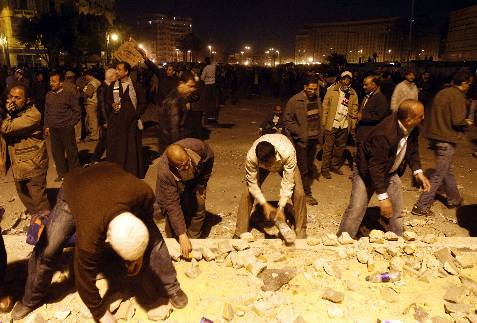 Manifestantes antiMubarak a la procura de piedras. AFP PHOTO/MOHAMMED ABED