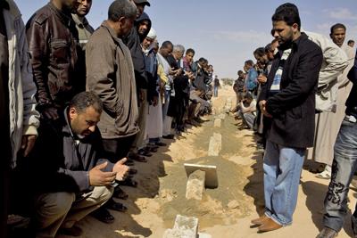 Familiares de las víctimas de los ataques aéreos del día anterior en Briga, rezan durante el funeral celebrado en la localidad de Ajdabiya.- EFE/STRINGER