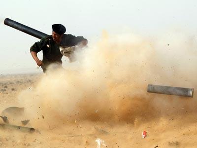 Un miliciano rebelde dispara una cañón, ayer, durante la batalla de Ras Lanuf.