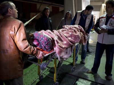 Varias personas evacúan a una mujer herida en Misrata hacia Bengasi, ya que los hospitales de la ciudad no pueden hacer frente al número de heridos.