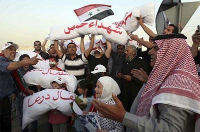 Un grupo de sirios con cadáveres de pega, envueltos en tela, grita consignas contra el presidente sirio Bachar al Asad. -