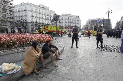 Varios policías vigilan a los 'indignados' acampados desde el 23 de julio en la Puerta del Sol, en Madrid, que han sido desalojados esta mañana por las fuerzas de seguridad, mientras los servicios municipales de limpieza retiran los residuos de la zona.