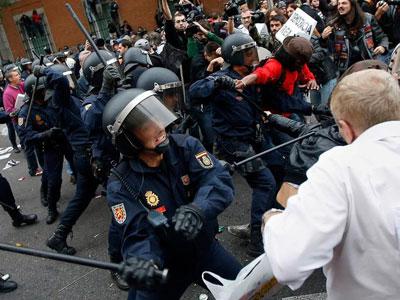 Un agente se prepara para golpear a un manifestante.