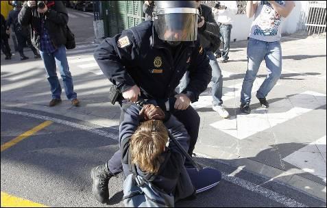 Un policía forcejea con un joven.