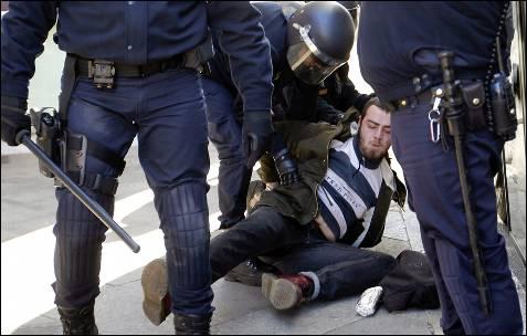 Un joven es retenido en el suelo por varios agentes.