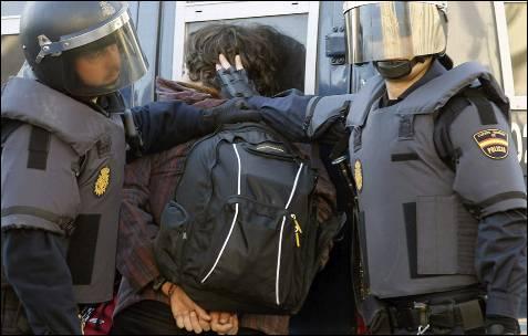 Dos antidisturbios ponen contra la pared a un joven esposado.
