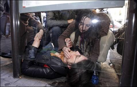 Una mujer atiende a una joven herida tras las cargas policiales en Valencia.
