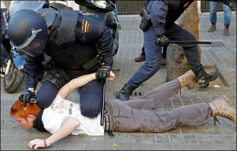 Un agente detiene a un joven al que previamente ha inmovilizado en el suelo.