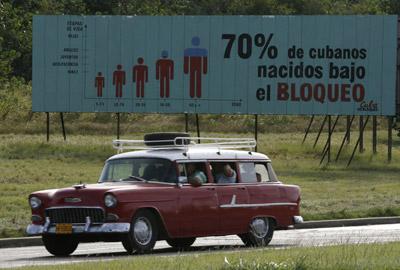 Un coche pasa en La Habana junto a un cartel que recuerda que el 70% de cubanos ha nacido bajo el bloqueo. -