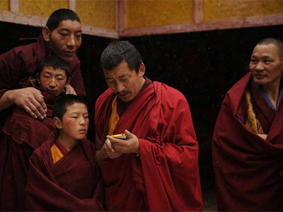 Monjes tibetanos con un Iphone. AFP PHOTO/Peter PARKS