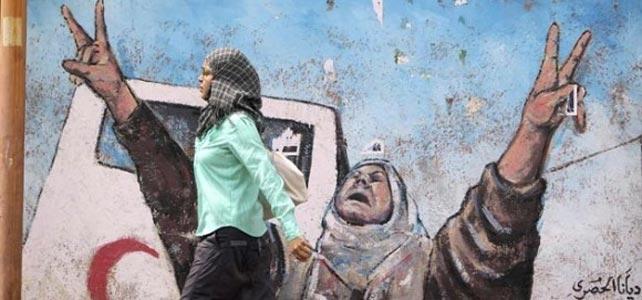 Una mujer pasa junto a un muro reinvidicativo en Gaza. REUTERS