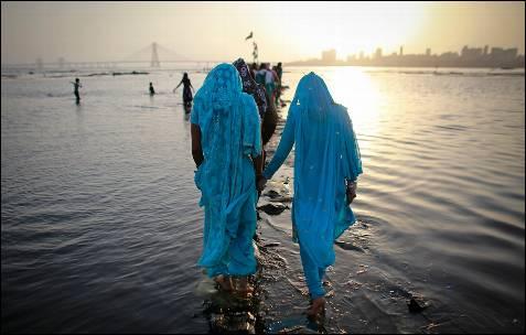 Varias personas caminan por una senda hecha de bolsas de cemento para ofrecer sus oraciones en un santuario en Bombay.