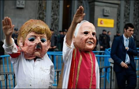 Dos personas con mascaras se hacen pasar por la canciller alemana Angela Merkel y el Papa, durante una manifestación en Madrid contra la reforma educativa, conocida como Ley Wert.