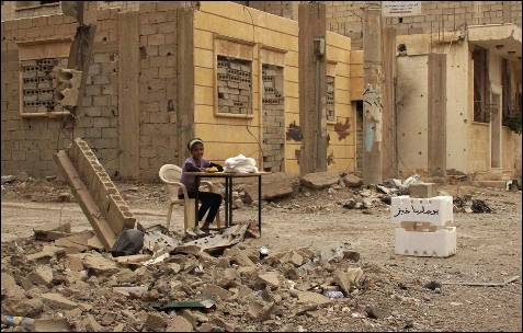 Una niña sentada en una silla colocada entre escombros, vende pan en una calle en Deir al-Zor (Siria).