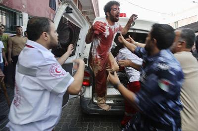 Un hombre manchado con la sangre de su padre muerto por un bombardeo israelí baja de una ambulancia en un hospital al sur de la Franja de Gaza.