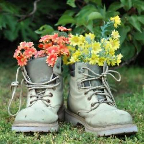 imagen de unas botas usadas como maceta de flores