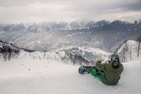 Chico haciendo snowboard y descansando en la cima de la montaña nevada