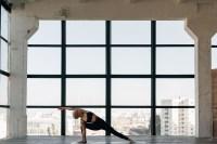 Mujer haciendo yoga frente a un gran ventanal