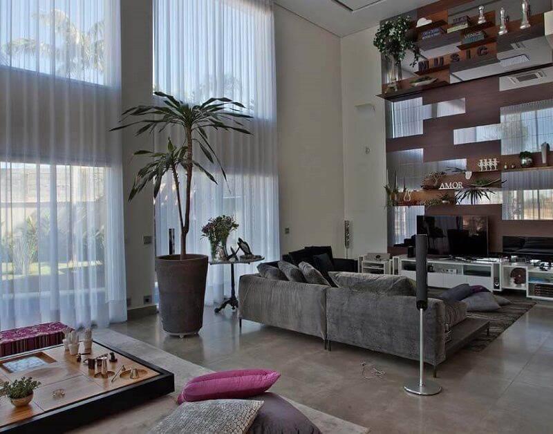 sala planejada com estante alta projeto de Guardini Stancati Arquitetura + Designer