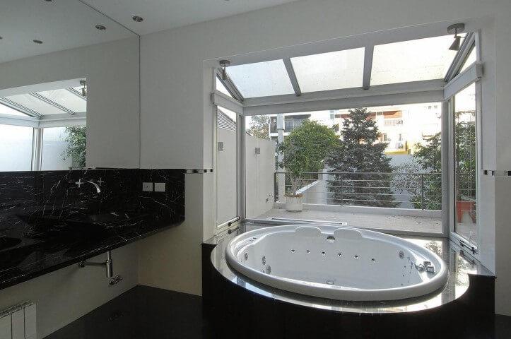 Banheiro de luxo com acabamento em vidro para entrada de luz natural Projeto de Estudio Sespede
