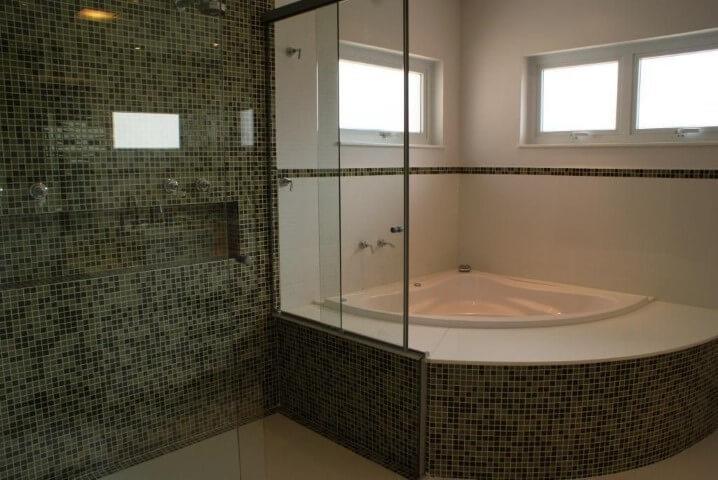 Banheiro de luxo com banheira e pastilhas escuras Projeto de Rosani Gomes