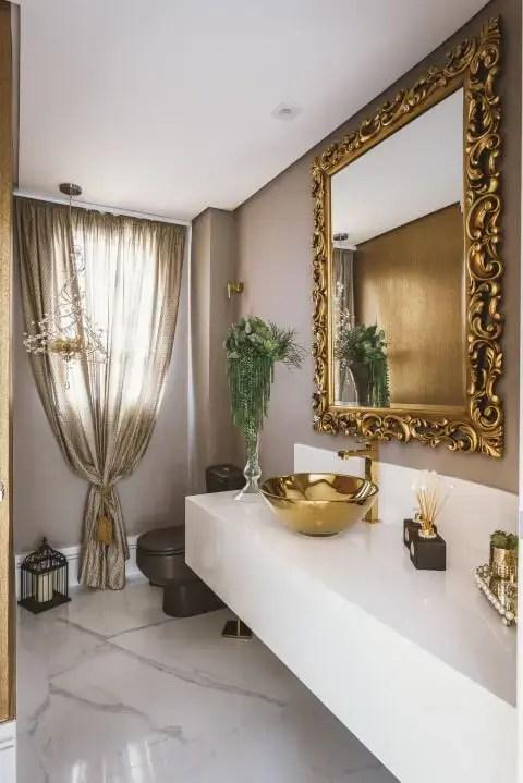 Banheiro de luxo com peças douradas Projeto de Daniela Gradella
