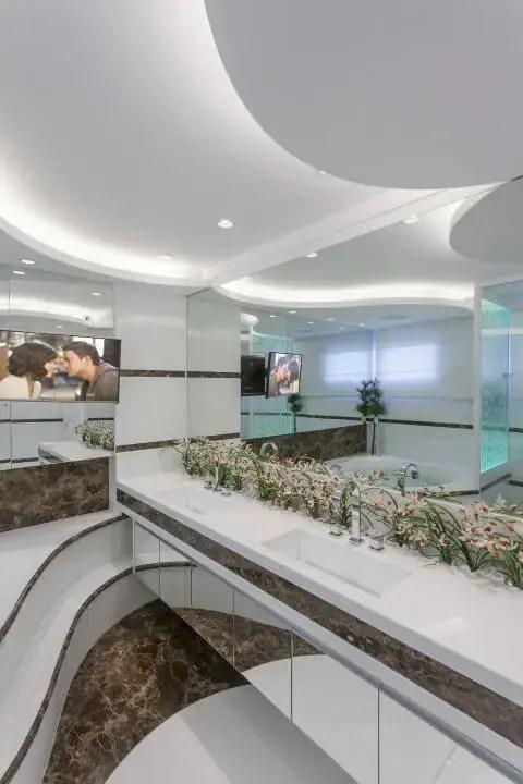 Banheiro de luxo em mármore marrom e branco e jardim Projeto de Iara Kilaris