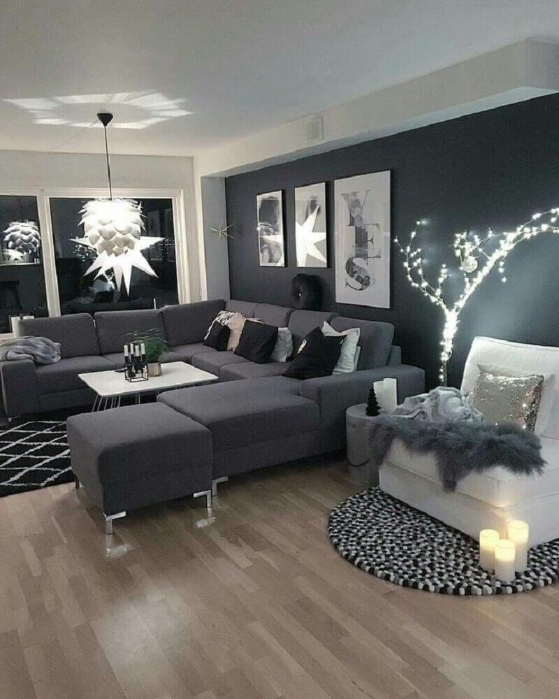 sala com parede preta e sof cinza