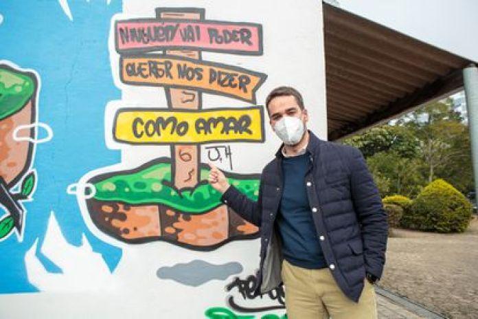 Eduardo Leite posa em frente a um grafite em homenagem ao orgulho LGBTQIA produzido pelo CJ Cruzeiro.