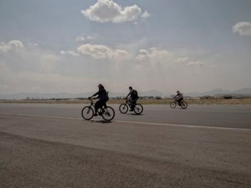 Several Taliban cycle on the runway at Hamid Karzai International Airport the morning after the United States officially leaves the country.