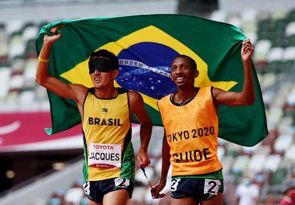 O campeão paralímpico Yeltsin Jacques com o atleta-guia Carlos Antonio dos Santos celebram a segunda medalha de ouro do corredor nos Jogos Paralímpicos de Tóquio.