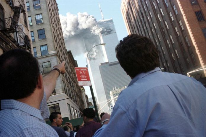 Pedestrians react to the World Trade Center collapse September 11, 2001. Two commercial airplanes cr..
