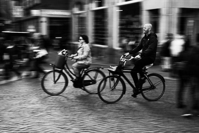 Registro feito durante viagem a cidade de Amsterdã, localizada nos Países Baixos. fotografia de pessoas em movimento em uma bicicleta em Amsterdã, na Holanda do Norte.