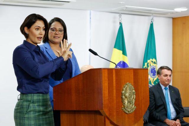 A primeira-dama, Michelle Bolsonaro, faz um pronunciamento na Língua Brasileira de Sinais (Libras), acompanhada de uma intérprete, durante a cerimônia de lançamento da Política Nacional de Educação Especial e Homenagem ao Mês dos Surdos
