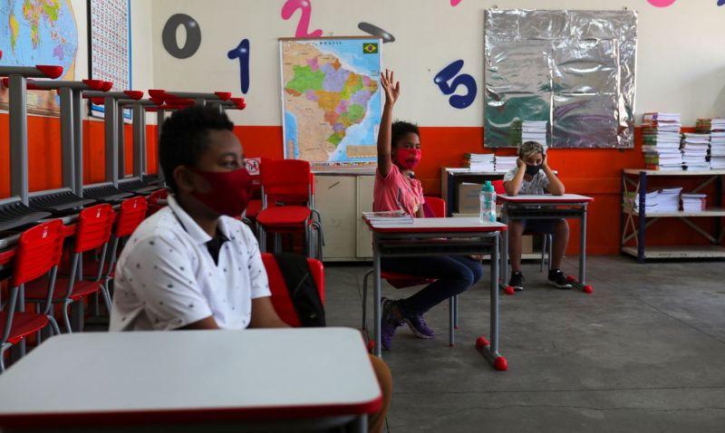Criança levanta a mão ao lado de outros alunos em sala de aula da escola Thomaz Rodrigues Alckmin, no primeiro dia de retorno das escolas do estado de São Paulo para atividades extracurriculares em meio ao surto de coronavírus (COVID-19) em São