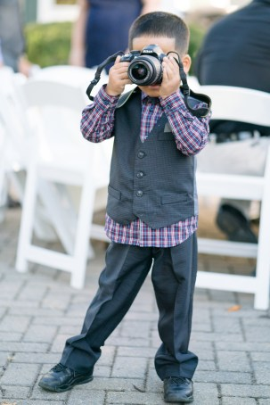 A little boy holds a camera during a wedding at Heritage Hunt Golf & Country Club in Gainesville, Virginia.