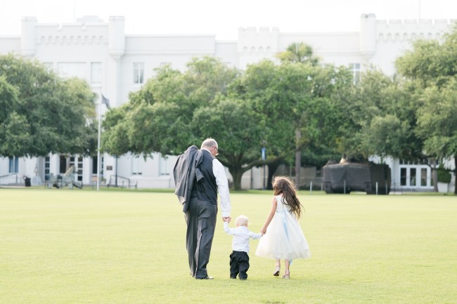 A grandfather and his two grandchildren walk hand-in-hand across a field during a wedding at The Citadel.